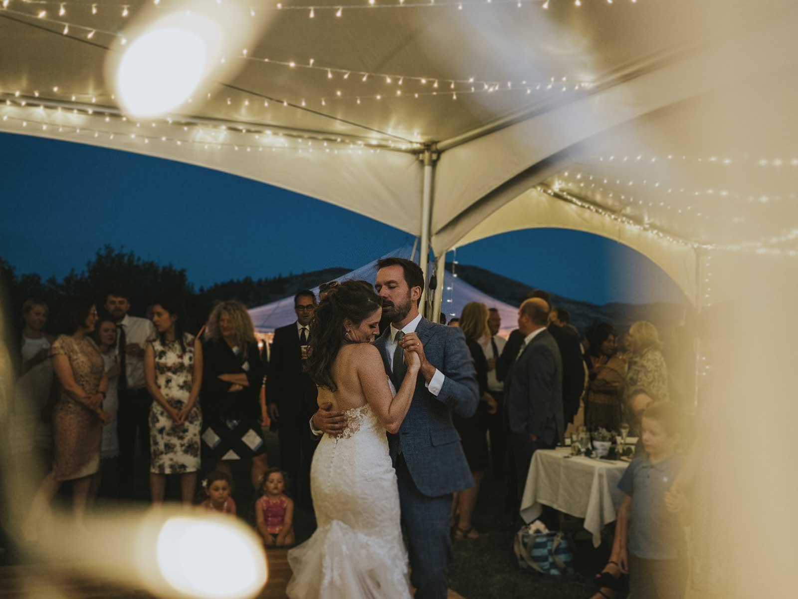 bride and groom dance under wedding tent