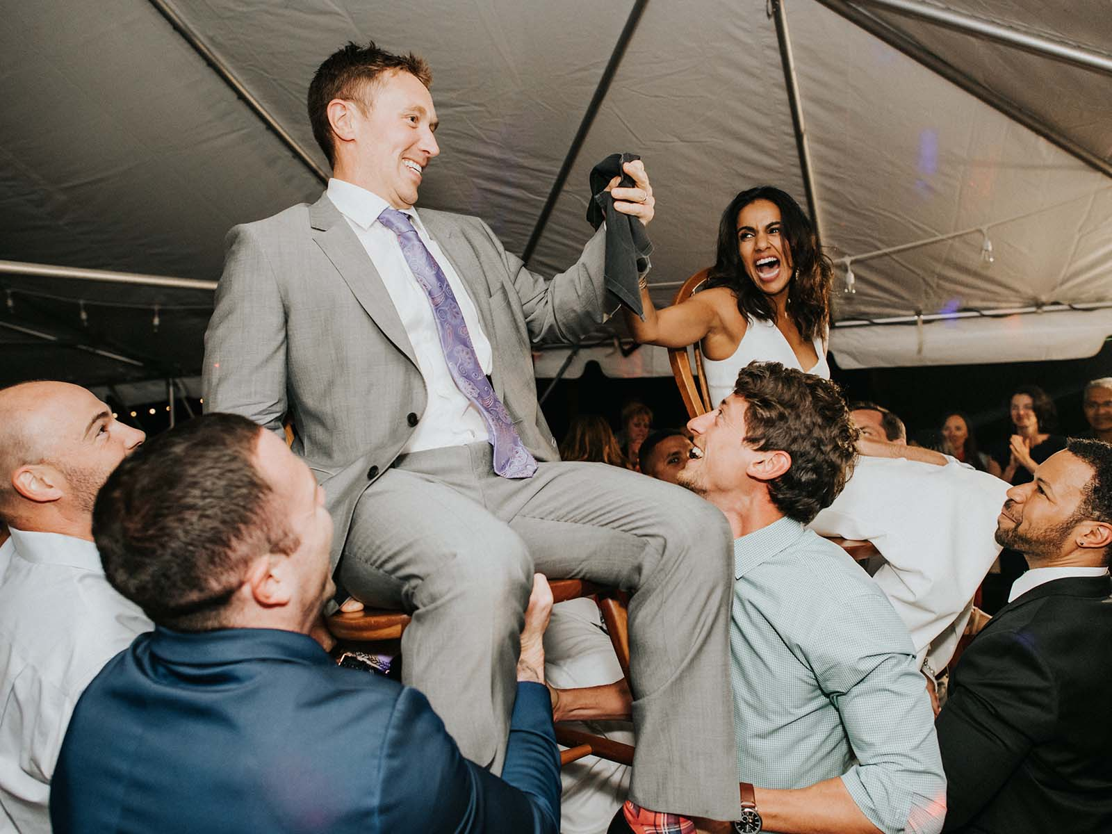 bride and groom lifted by groomsmen