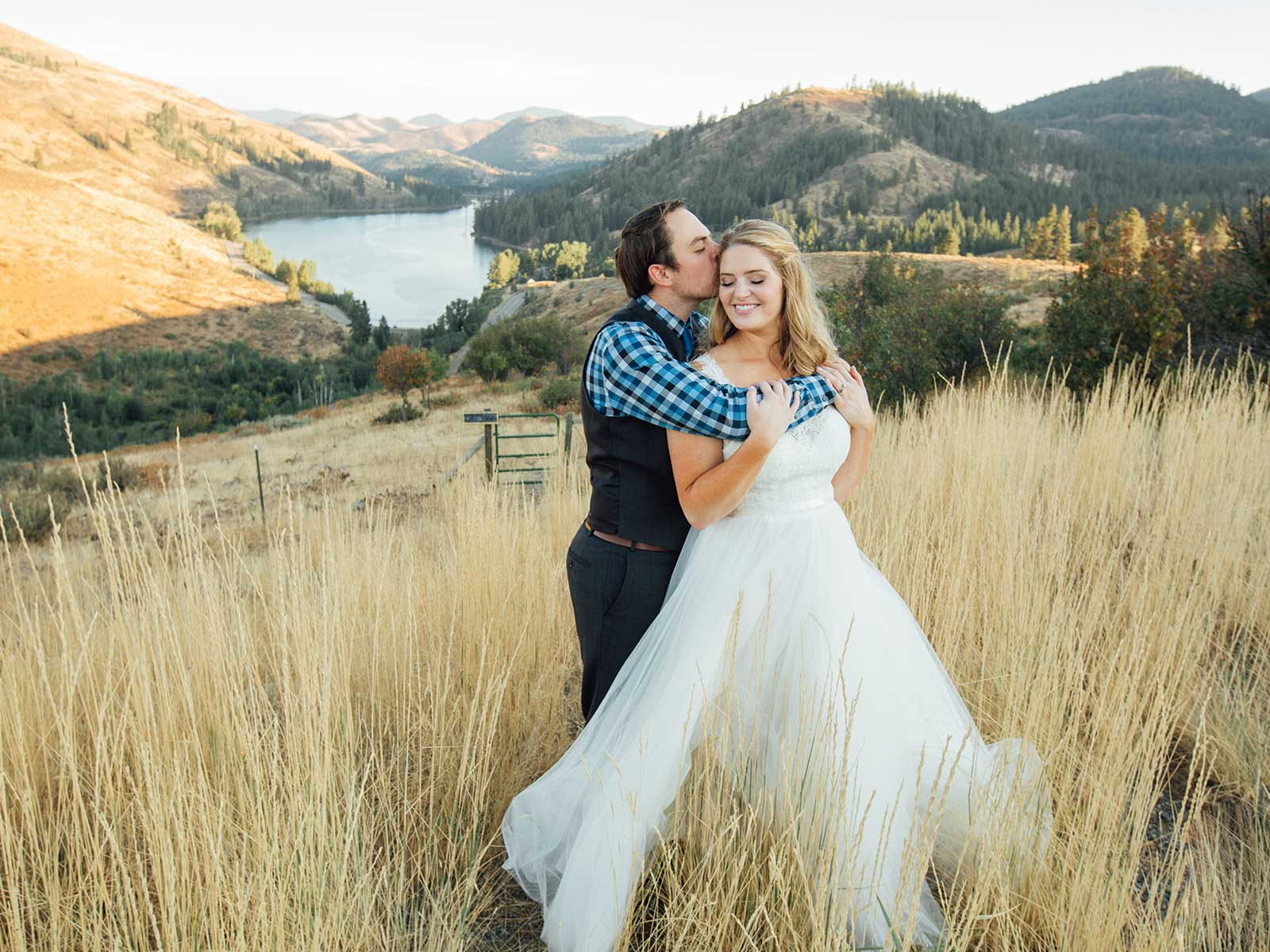 bride and groom in field with mountain view